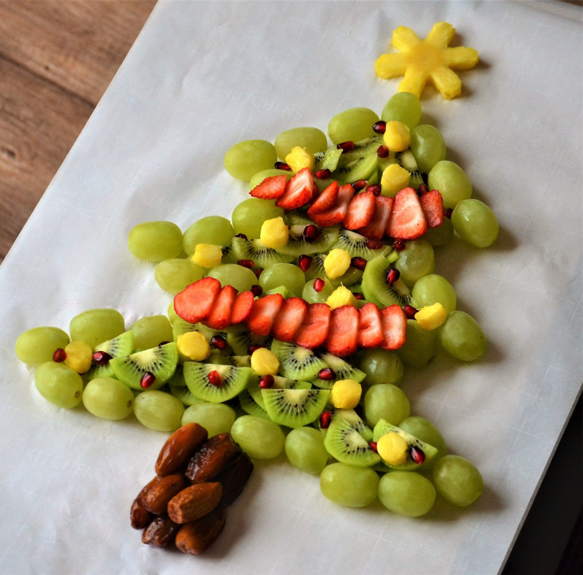 """""""Here's a festive way to serve fruit at your next holiday get-together! Do not prepare too far in advance of your party, or the fruit will dry out. You can mix up any leftover or scrap fruit to make a beautiful salad to serve alongside this Christmas tree fruit platter."""""""