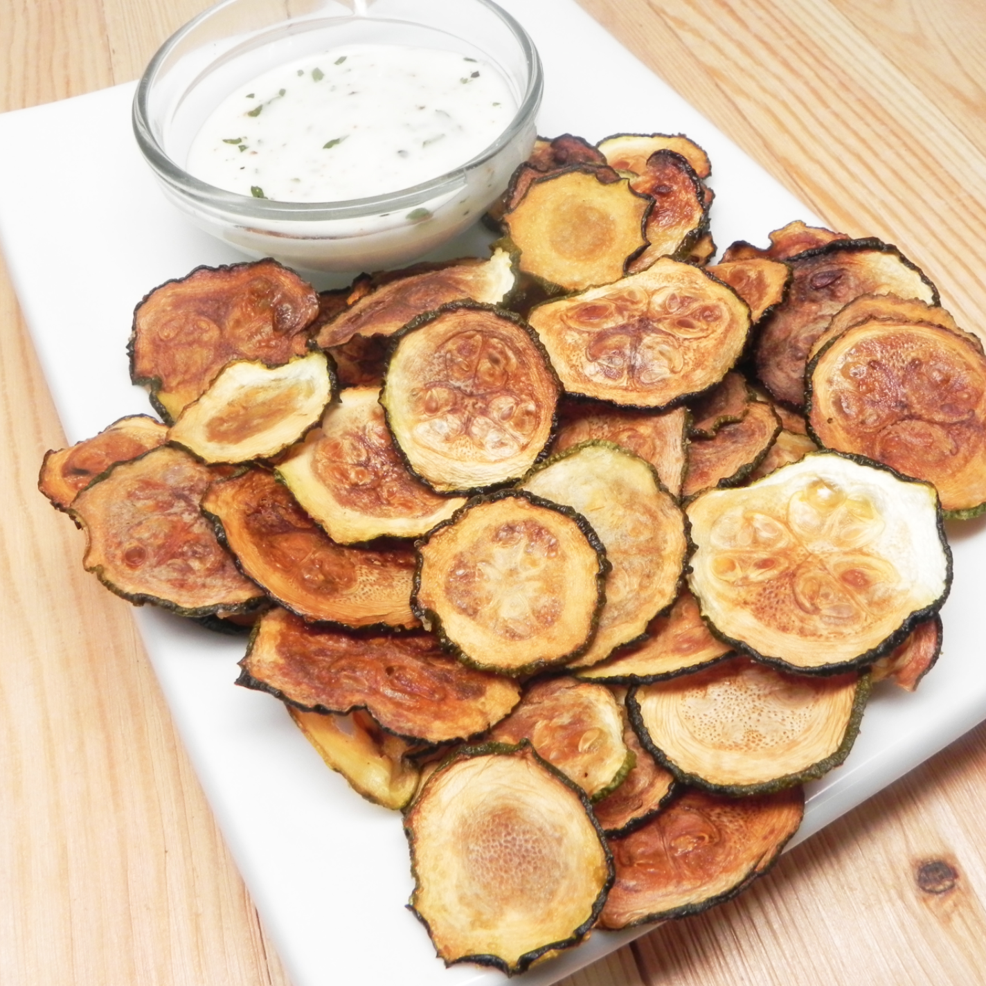 Low-Carb Zucchini Chips next to creamy dip nex