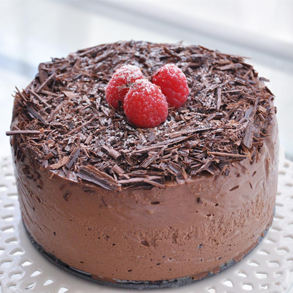 chocolate cappuccino cheesecake topped with fresh raspberries and chocolate shavings