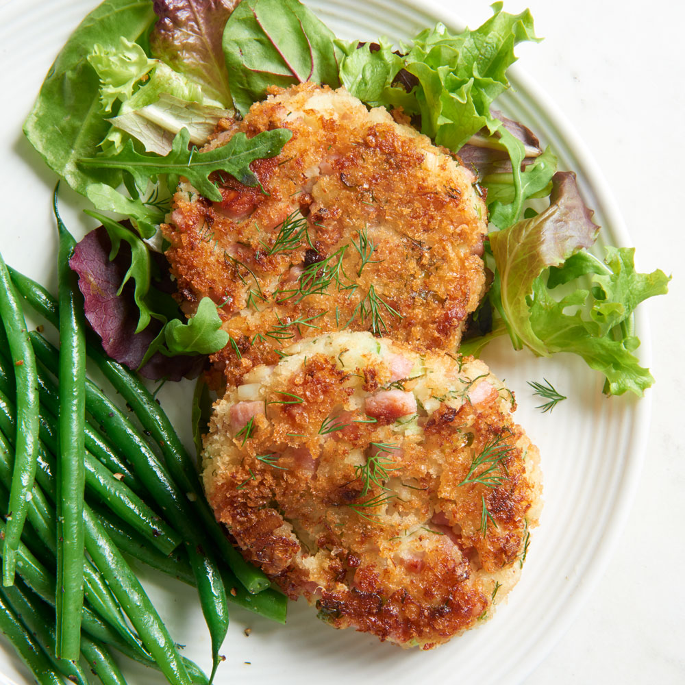 ham patties with wilted greens and green beans on modern white plate