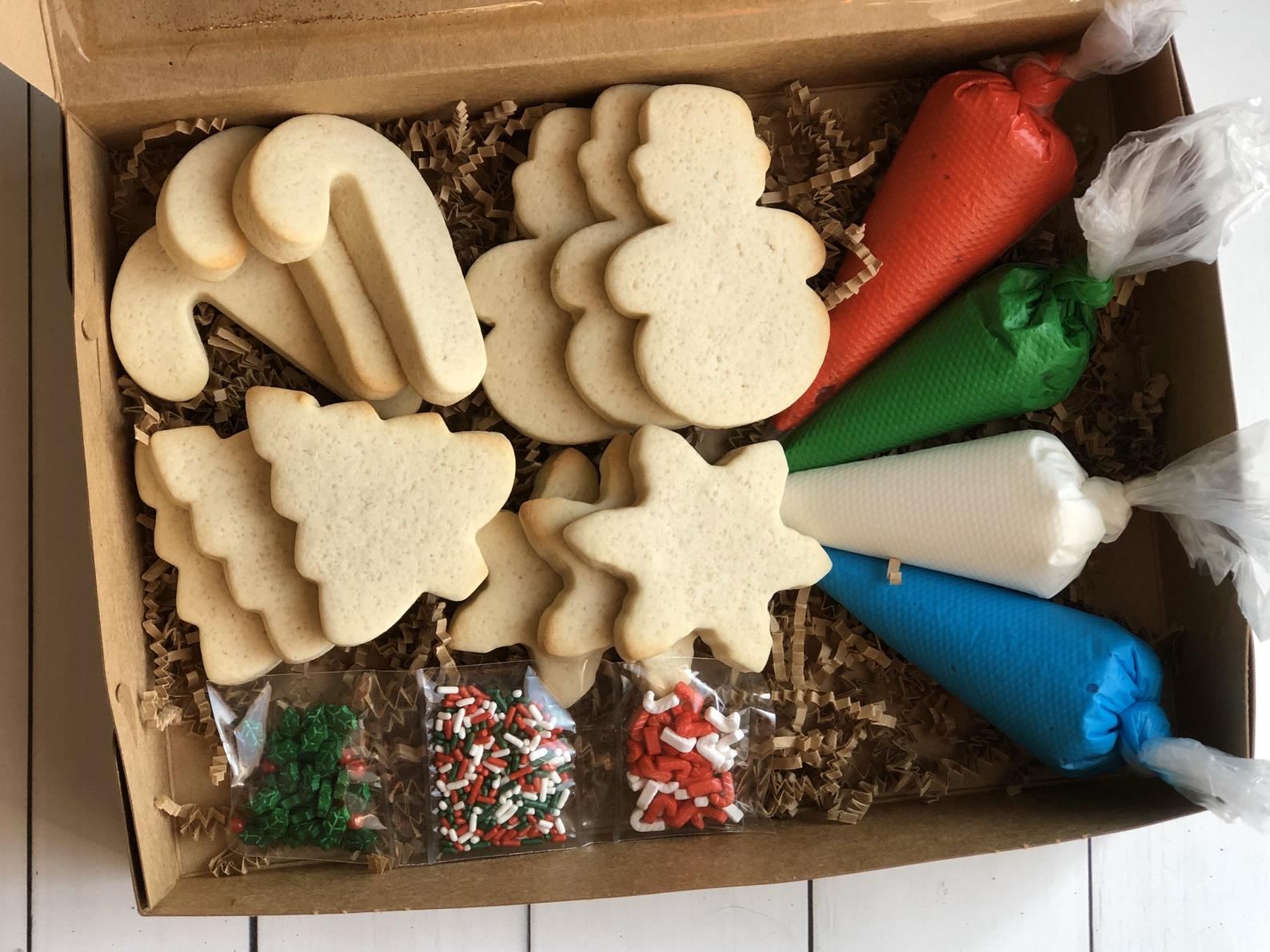 cardboard box with sugar cookies, icing in piping bags, and sprinkles inside