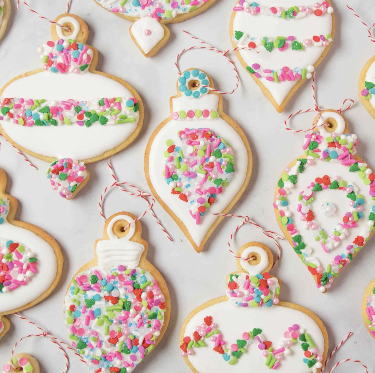 Ornament-shaped cookies with white icing and colorful sprinkles