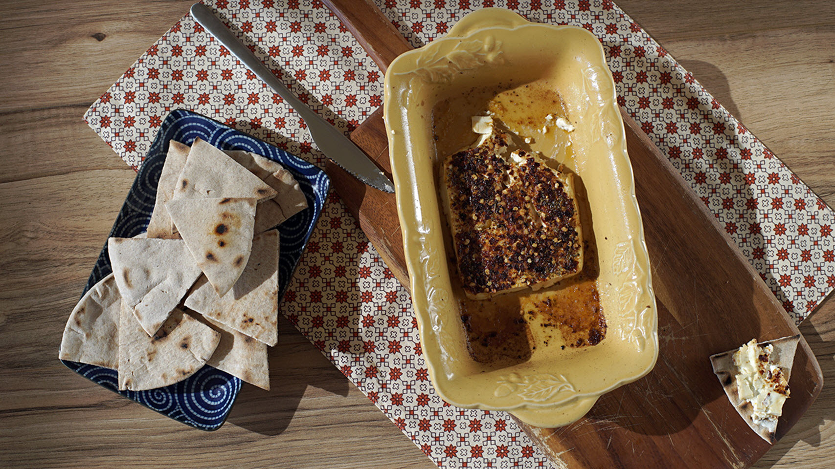 small baking dish with baked feta topped with lots of red chili flakes and pita bread on the side