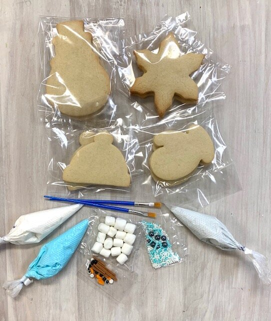 Set of plain sugar cookies, piping bags with icing, tools, and marshmallow/ and sprinkle toppings