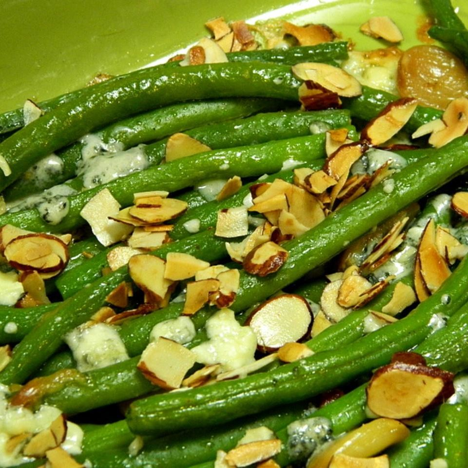 dish of green beans topped with slivered almonds and blue cheese