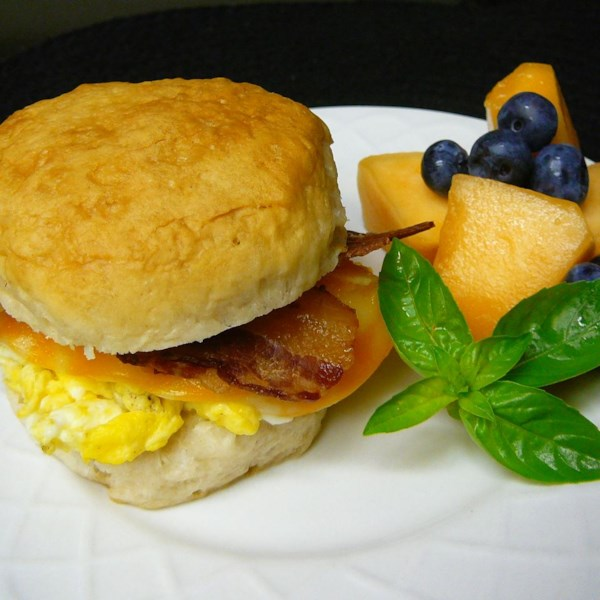 breakfast sandwich on white patterned plate with fruit accompaniment