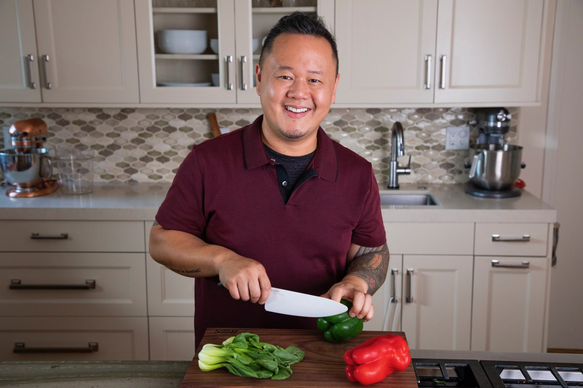 Jet Tila in the kitchen cutting into a bell pepper