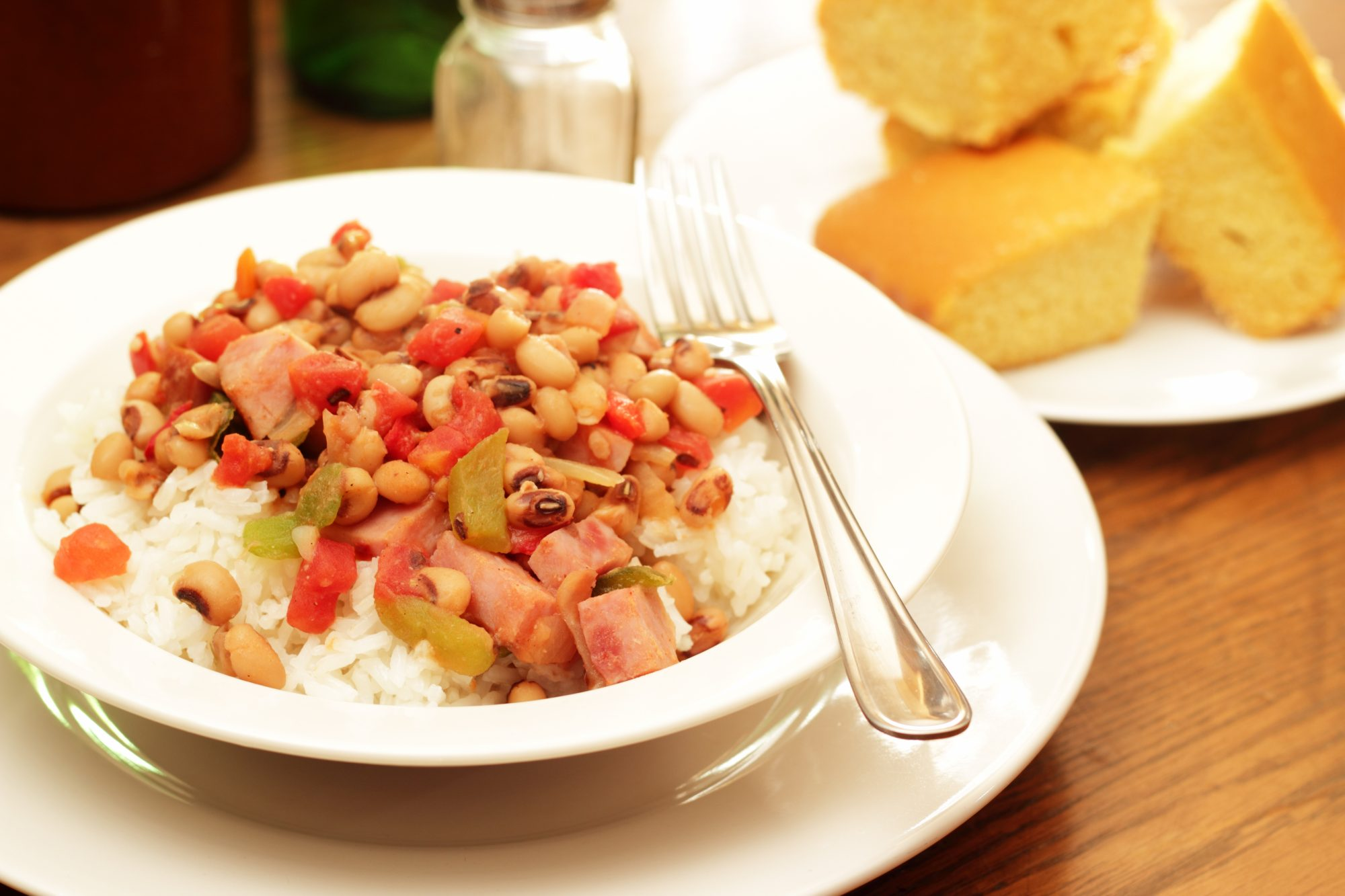 hoppin john in white bowl with fork and cornbread