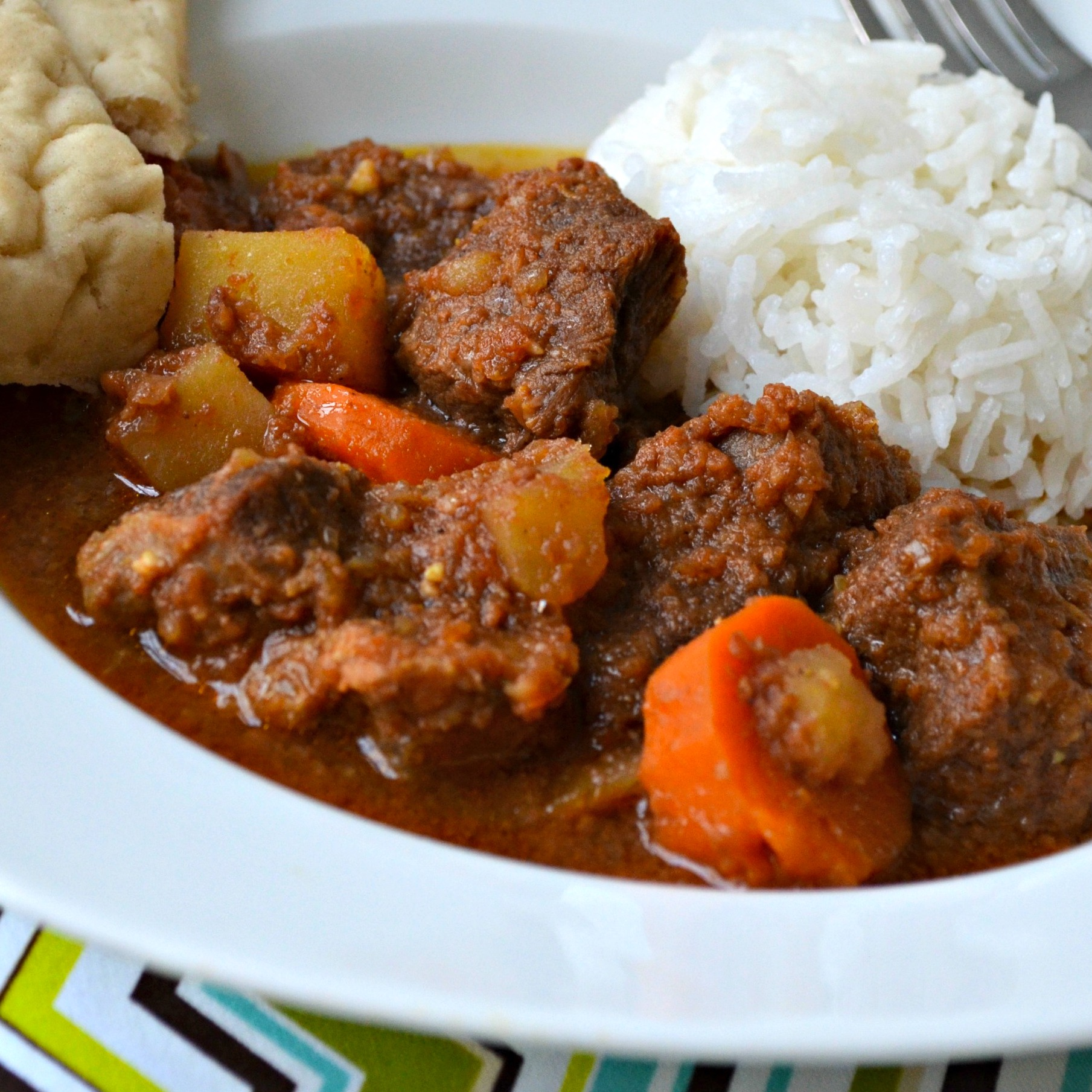 A chunky stew of meat, potatoes, and carrots in a bowl with a scoop of white rice, served with flatbread