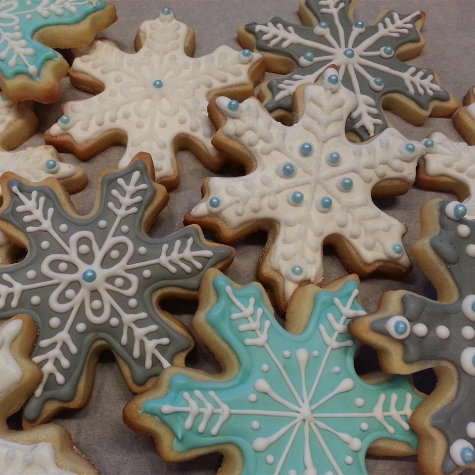 snowflake-shaped cookies decorated with white, pale blue, and gray frosting