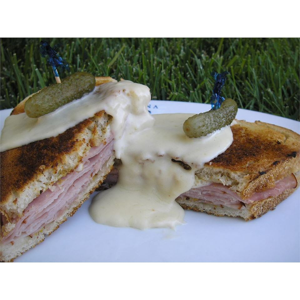 fried ham and cheese sandwich with béchamel puree over . cornichon garnish