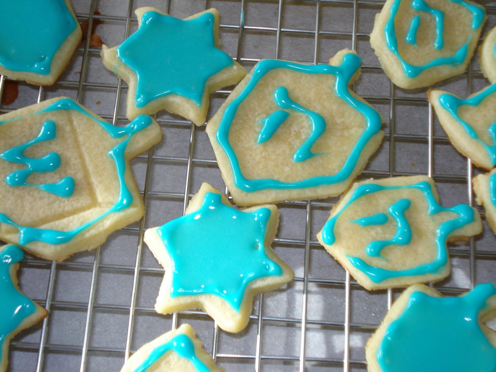 Chanukkah cookies decorated like dreidels and Stars of David with blue icing