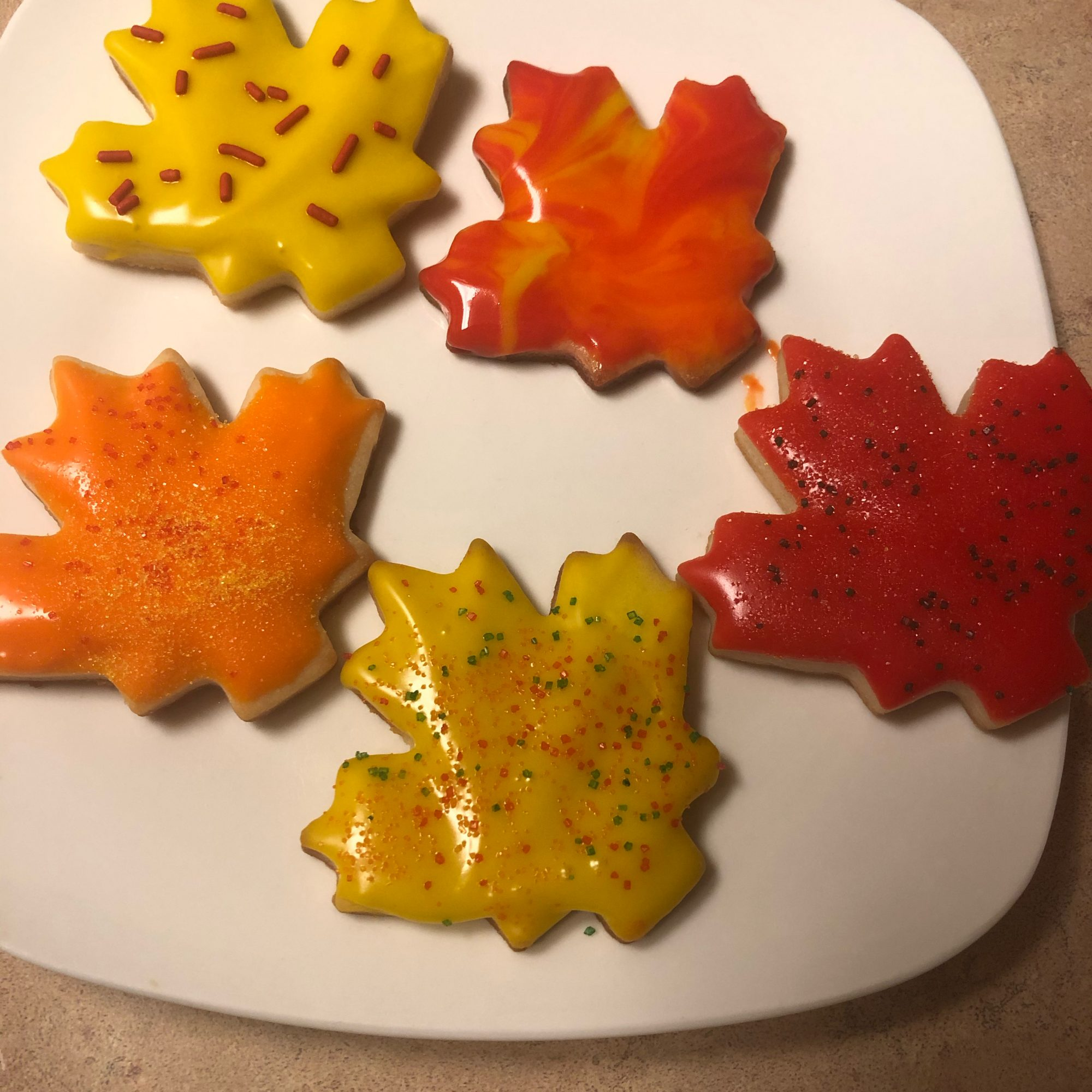 maple leaf-shaped cookies decorated for fall with orange, yellow, and red colors
