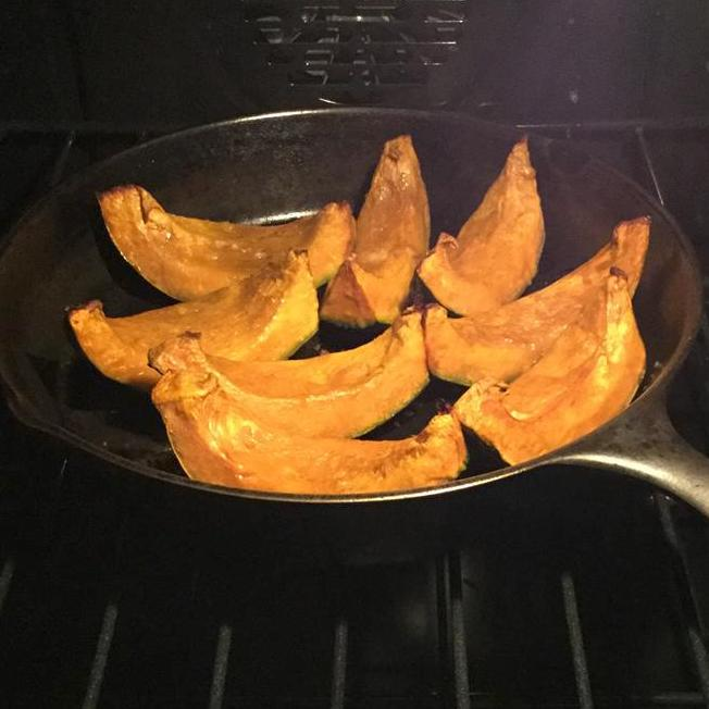 kabocha squash roasted in a pan in the oven