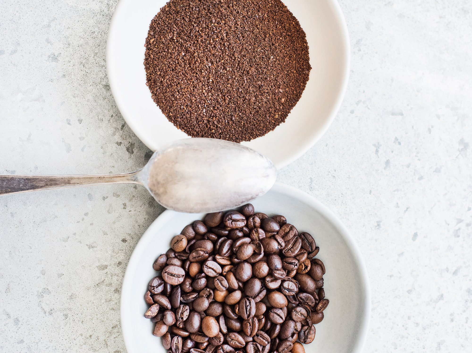 Coffee beans and ground coffee in bowls