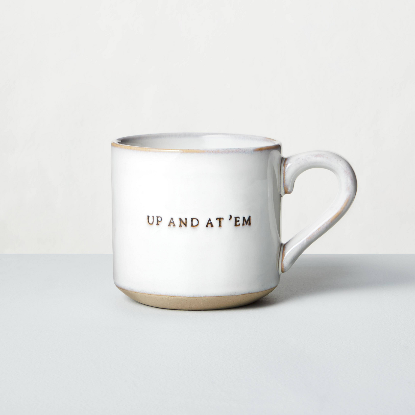 White stone mug with up and at em etched on it