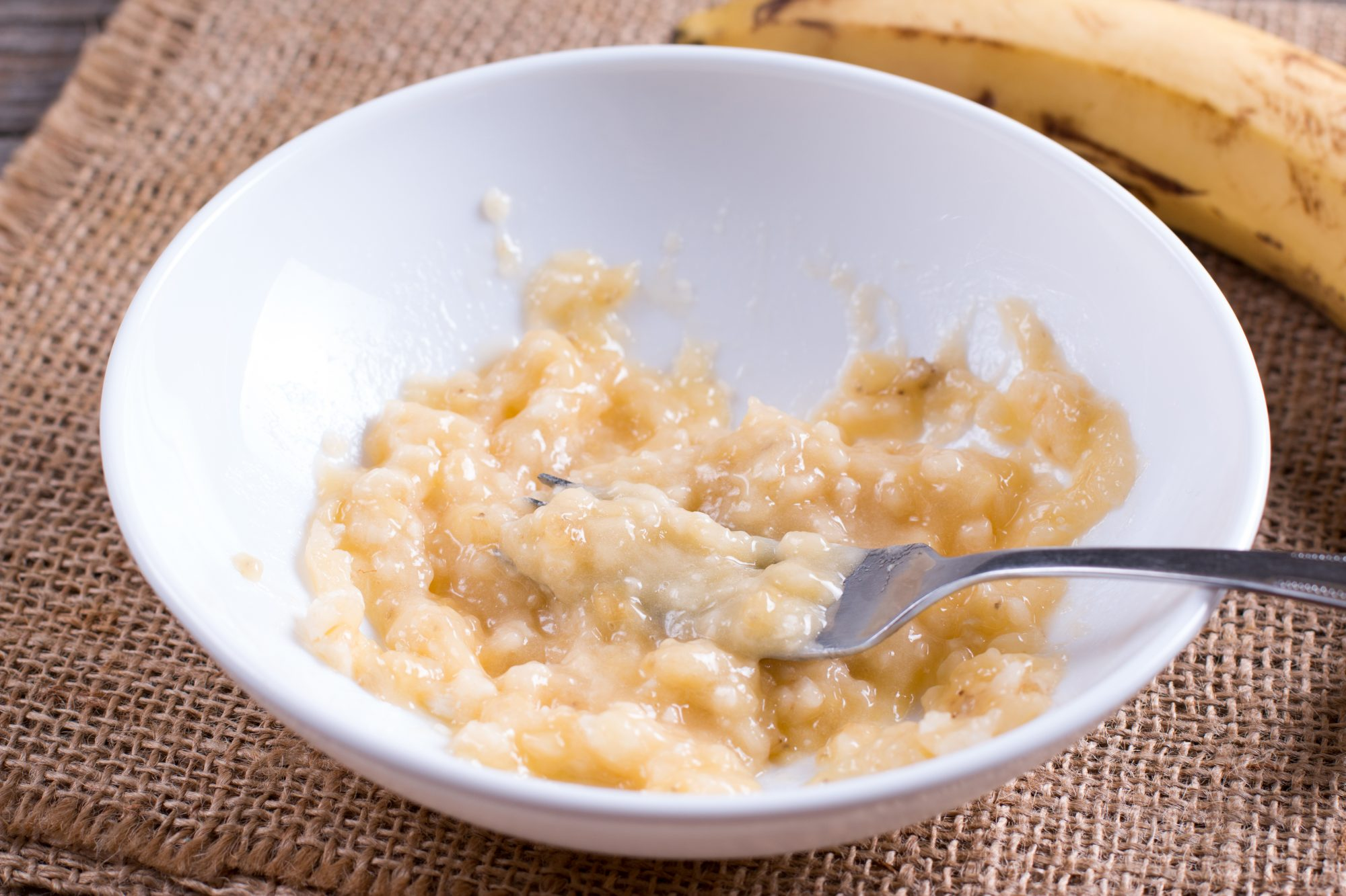 Slices of banana in a bowl and fork
