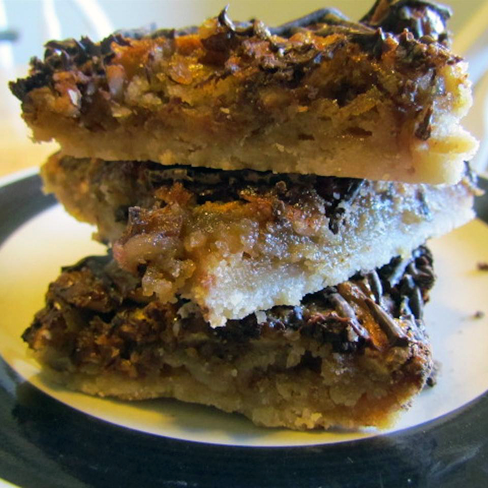 closeup of three pecan bars stacked on a plate