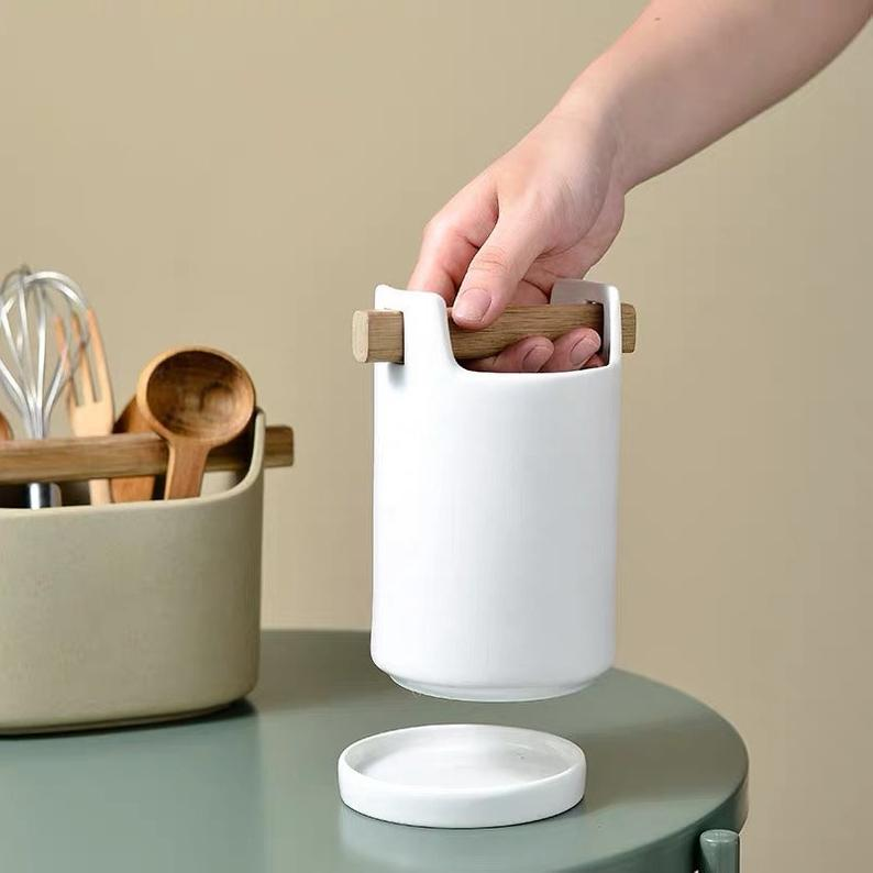 two ceramic utensil holders in tan and white