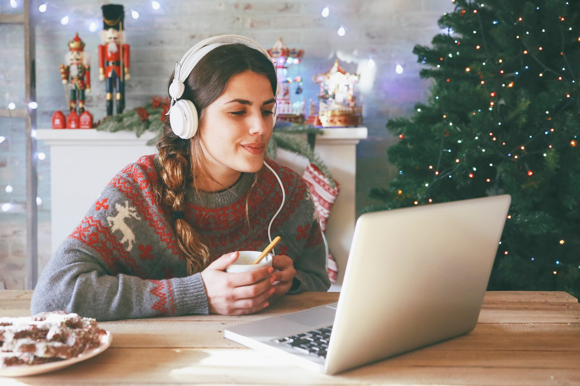Woman with cup of coffee using laptop and headphones at Christmas time
