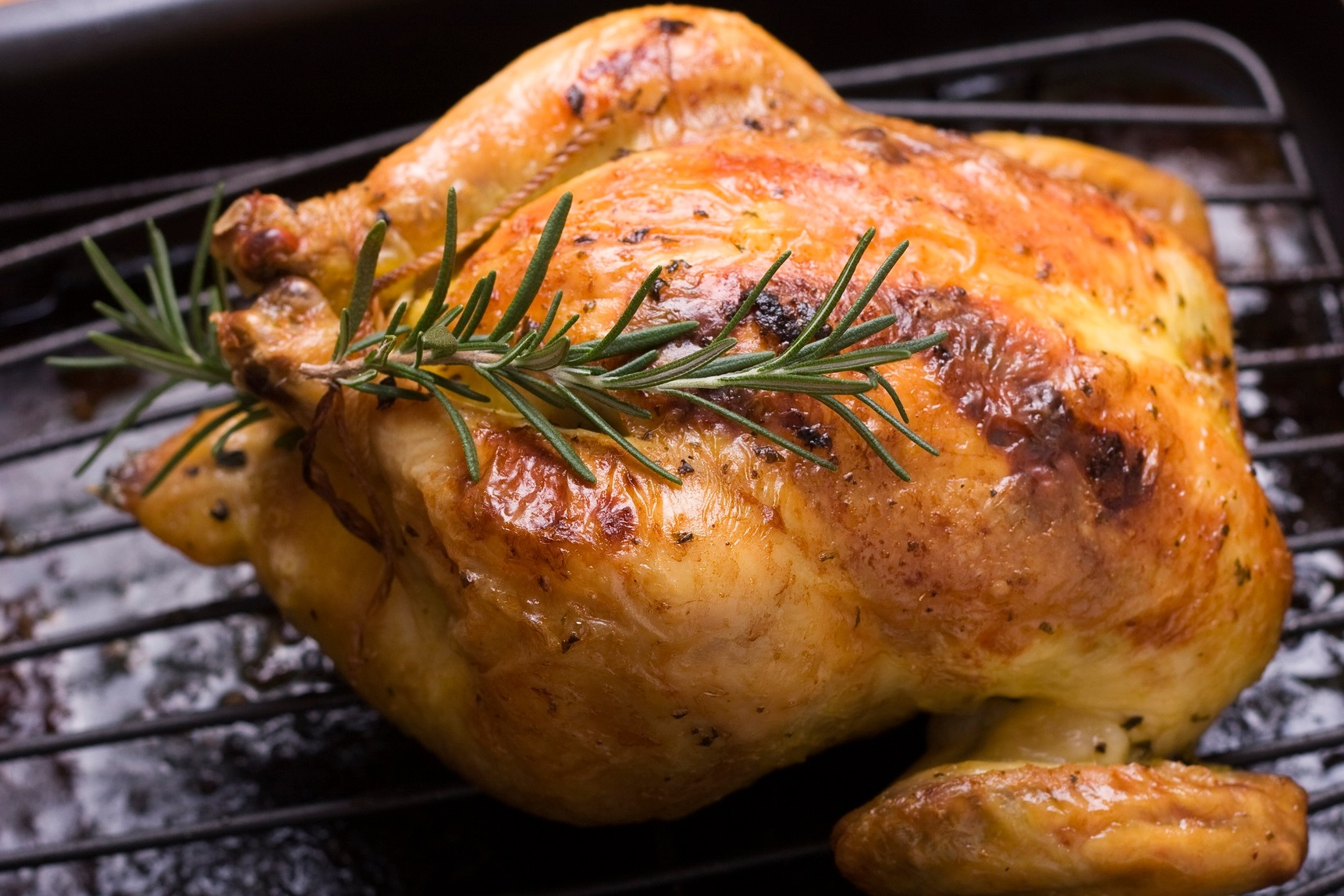 roasted cornish game hen garnished with rosemary sprig in a roasting pan