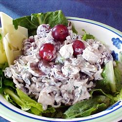turkey salad with wild rice and red grapes on a lettuce leaf