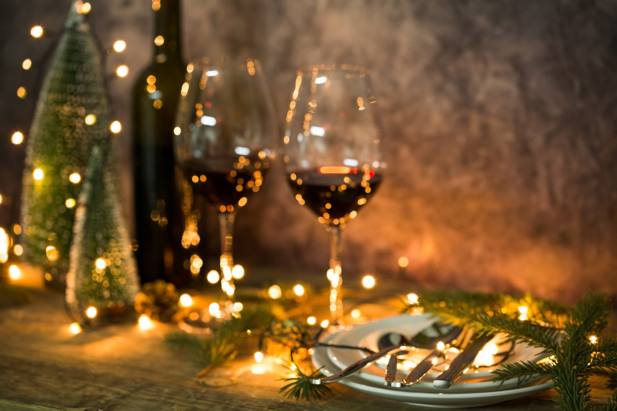 two wine glasses, plates, and christmas lights on a decorated christmas dinner table