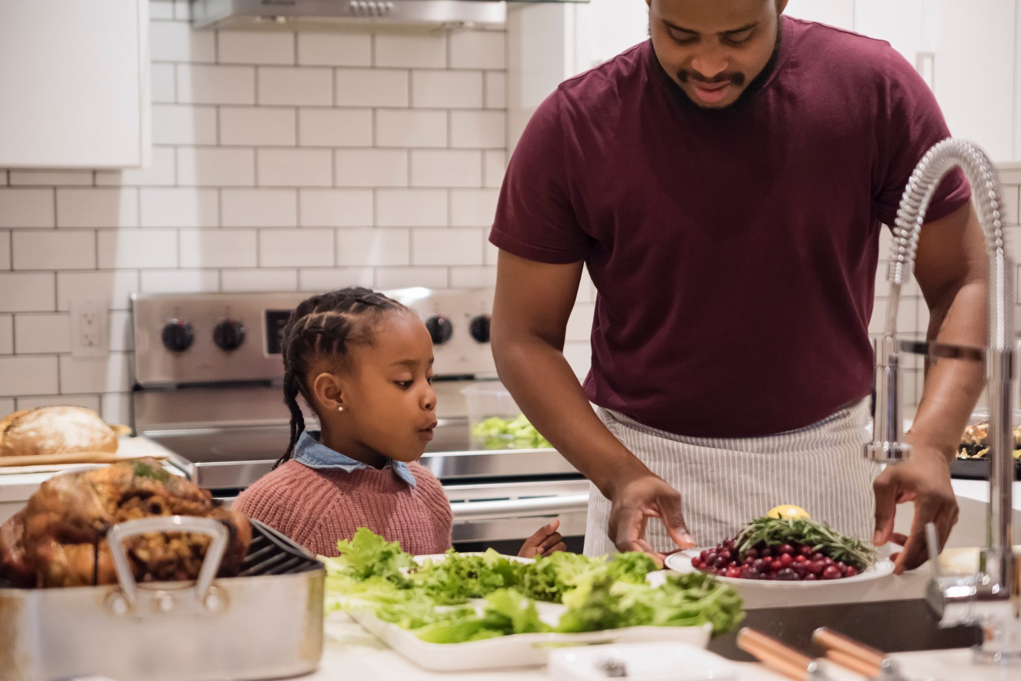 Father and young daughter preparing Thanksgiving dinner.