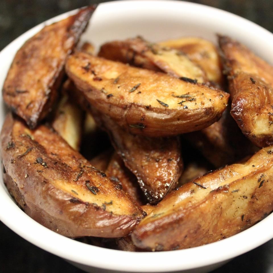 browned potato wedges with herbs in a white bowl