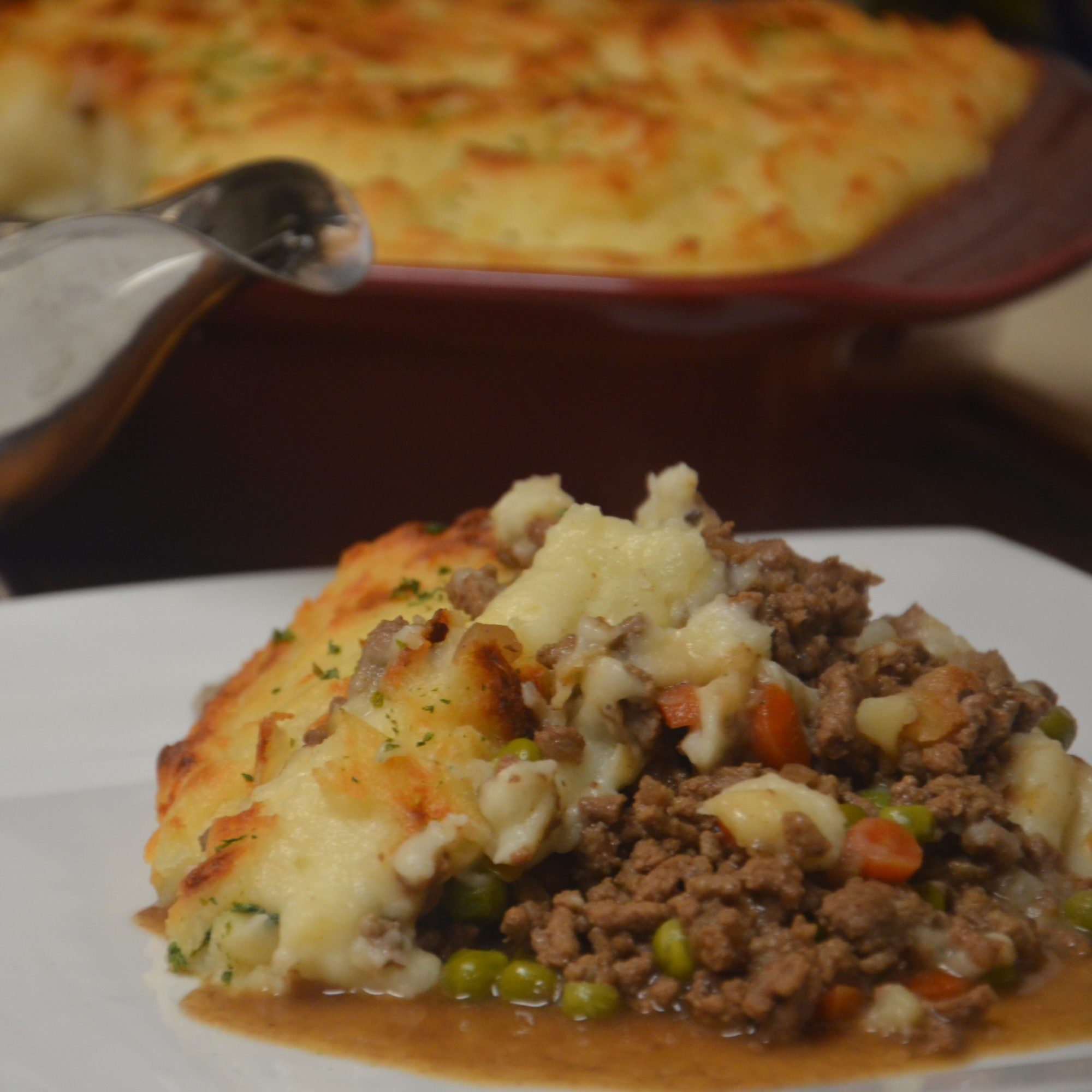 a serving of shepherd's pie on a white plate with the rest of the casserole in the background