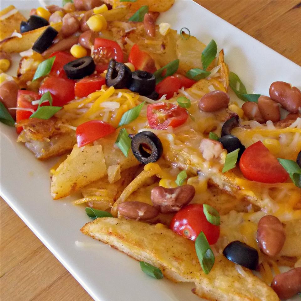 Potato wedges with nacho toppings on white platter