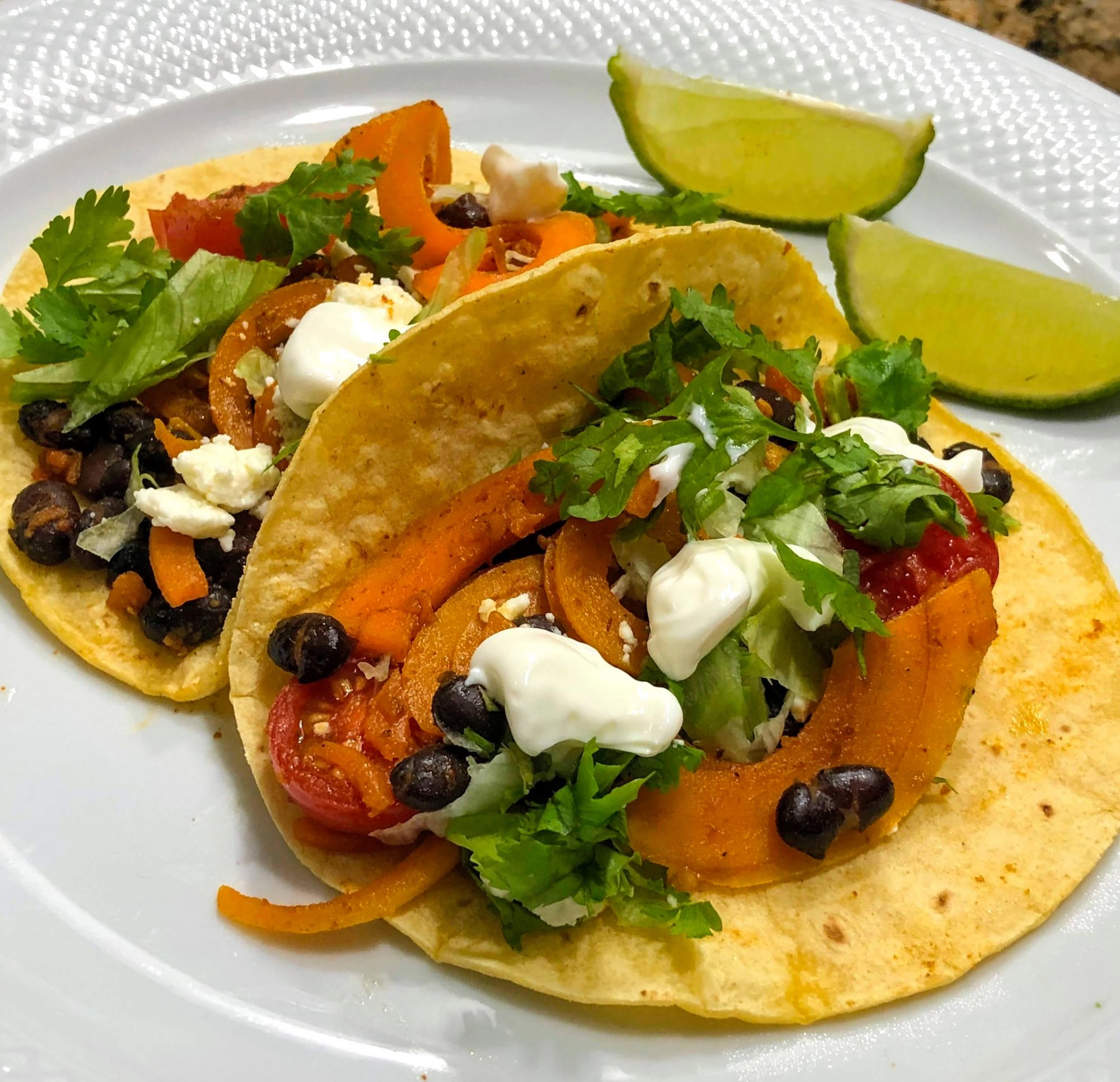 butternut squash and black beans with cheese and cilantro in taco shells