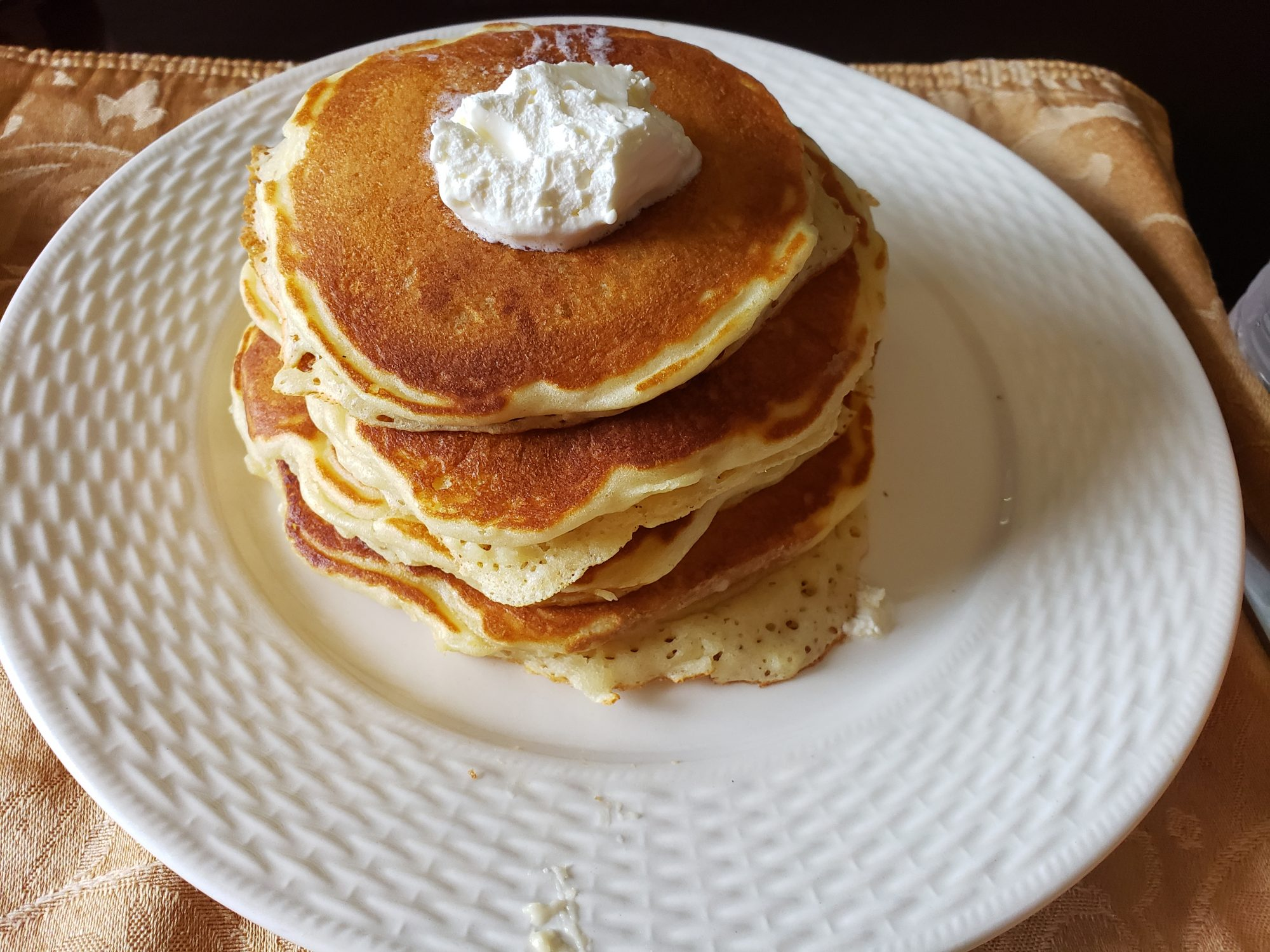 tilted overhead shot of whipped cream topped pancakes