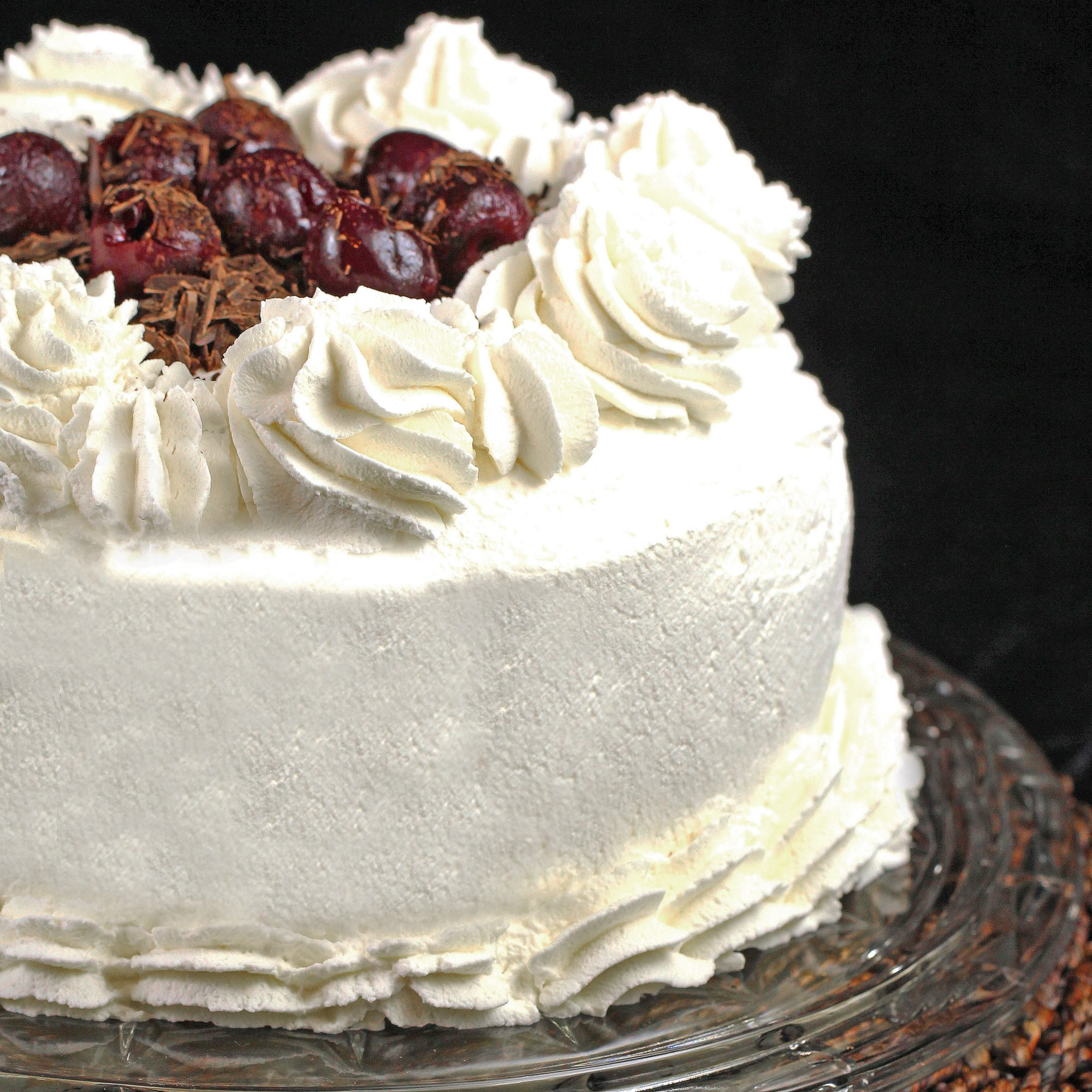 side view of a smooth white cream-coated Black Forest cake with rosettes of whipped cream and dark cherries in the center