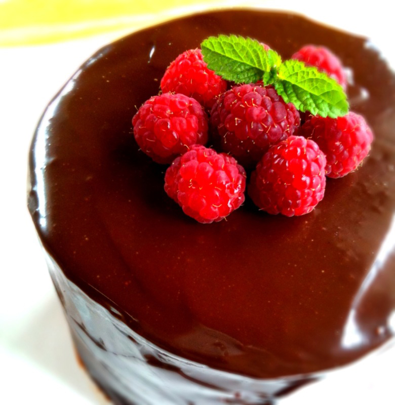 a top-down view of a smooth chocolate-glazed cake topped with a cluster of fresh raspberries and a mint leaf
