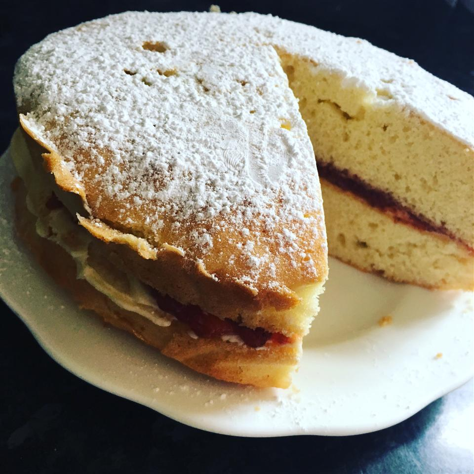 slightly tilted overhead shot of Victoria sponge cake with piece cut out