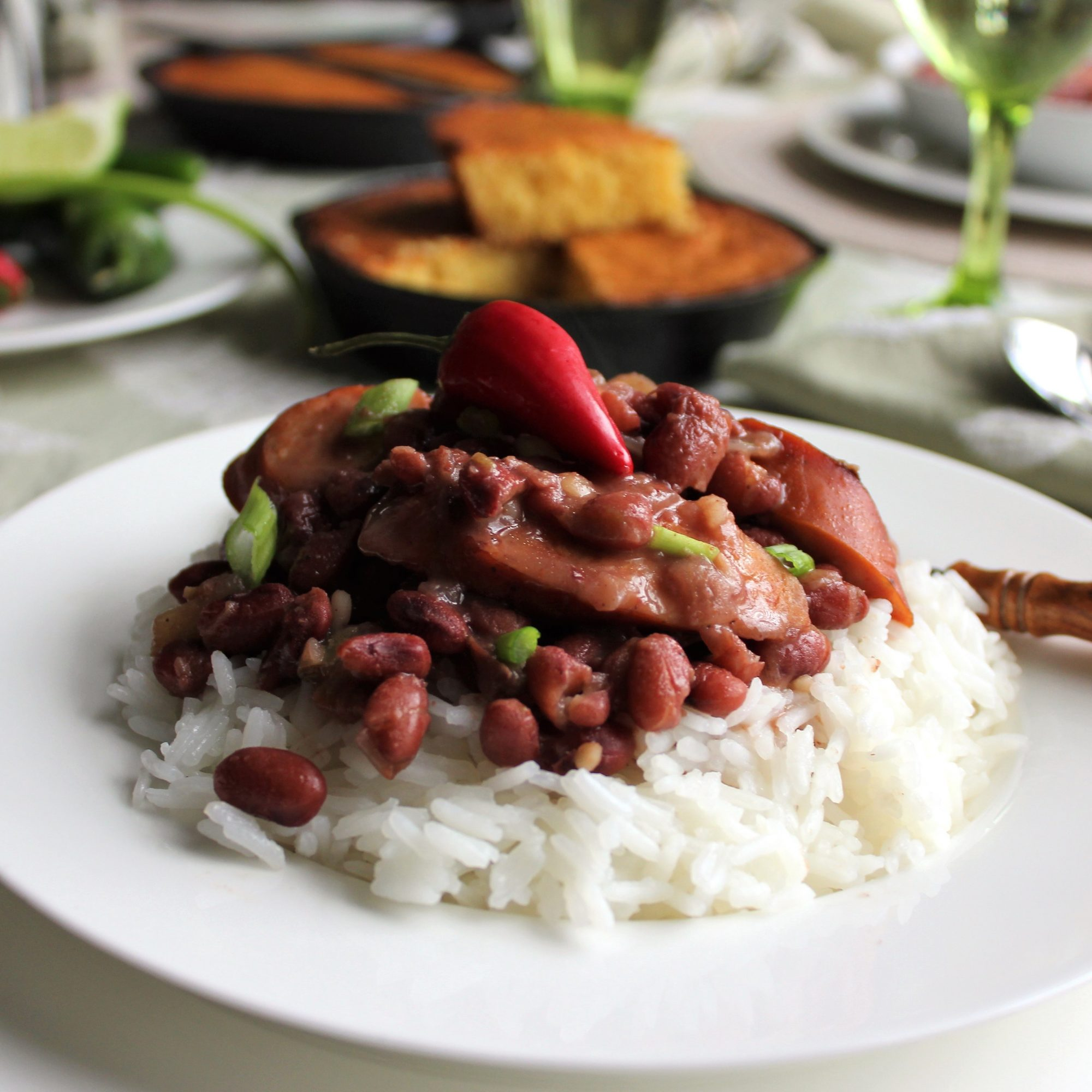 red beans and sausage over rice on a white plate
