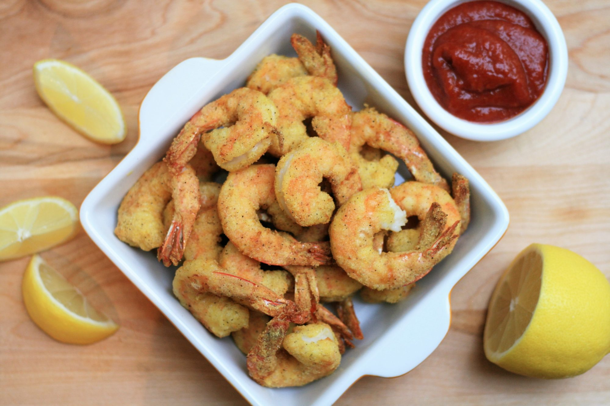 air. fryer shrimp in white bowl accompanied by cocktail sauce