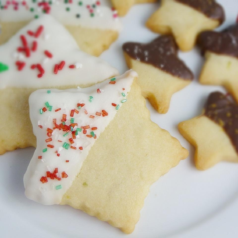 star-shaped shortbread cookies on a plate. Some are half-dipped in white chocolate sprinkled with red and green sugar, the rest are half-dipped in dark chocolate