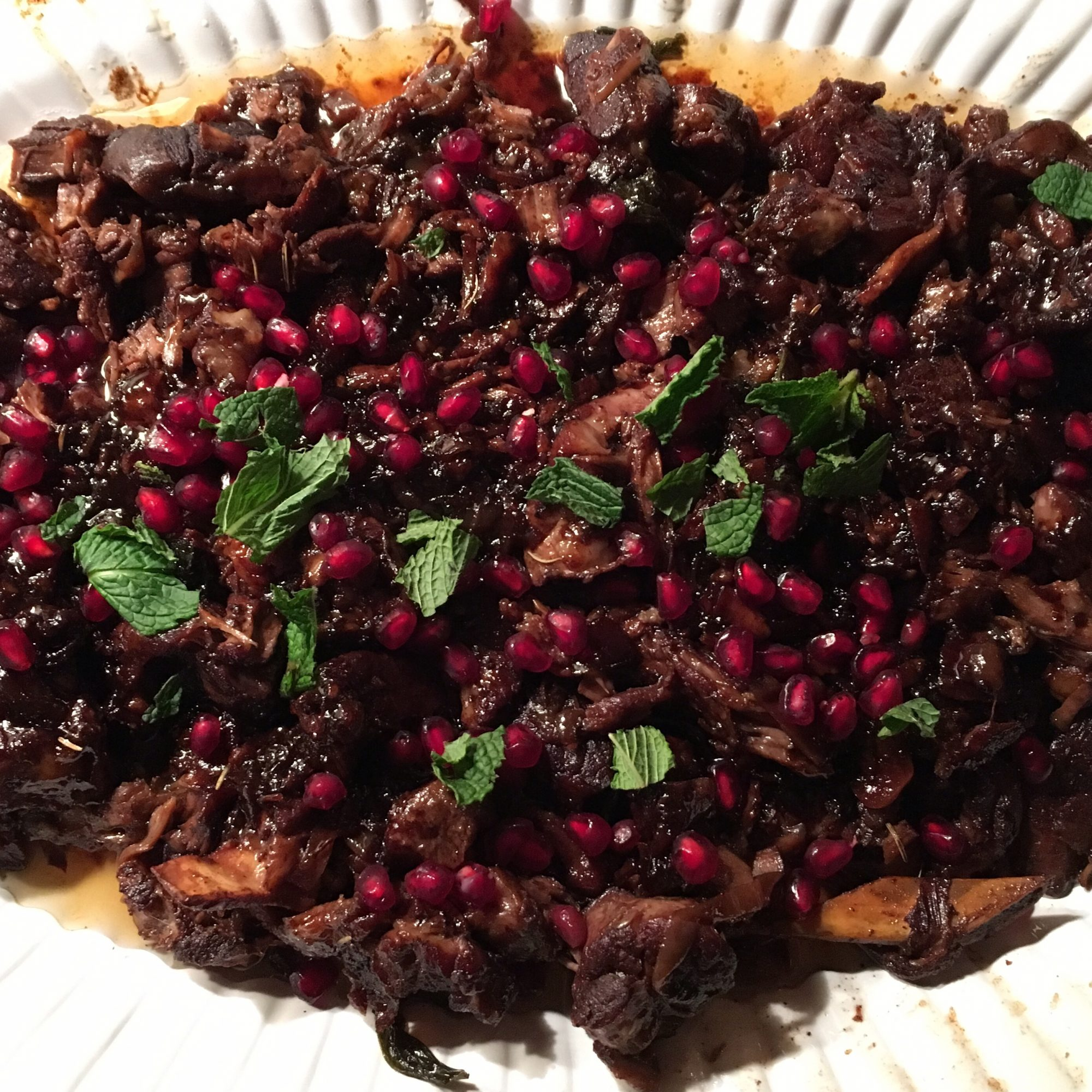 a platter of lamb chops garnished with pomegranate arils and fresh mint