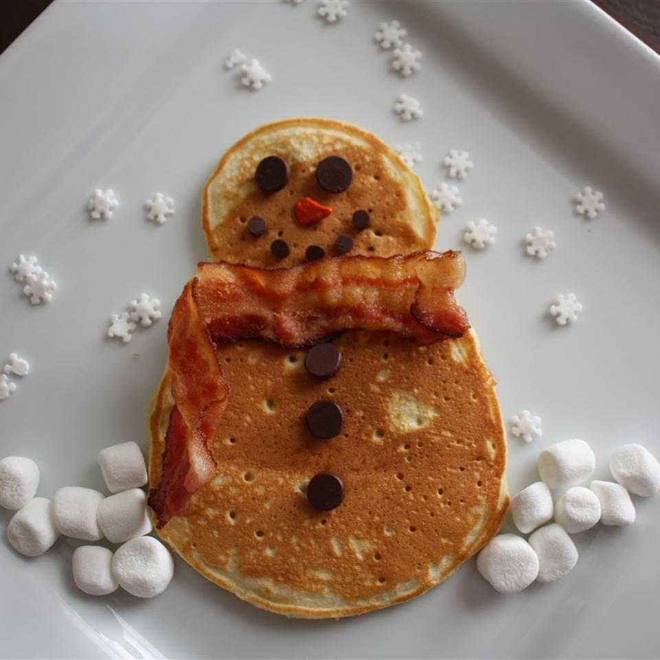 "a snowman-shaped pancake with chocolate chip and mini chip features and buttons and a bacon ""scarf"". The plate is garnished with mini marshmallow snow and snowflake-shaped sprinkles"