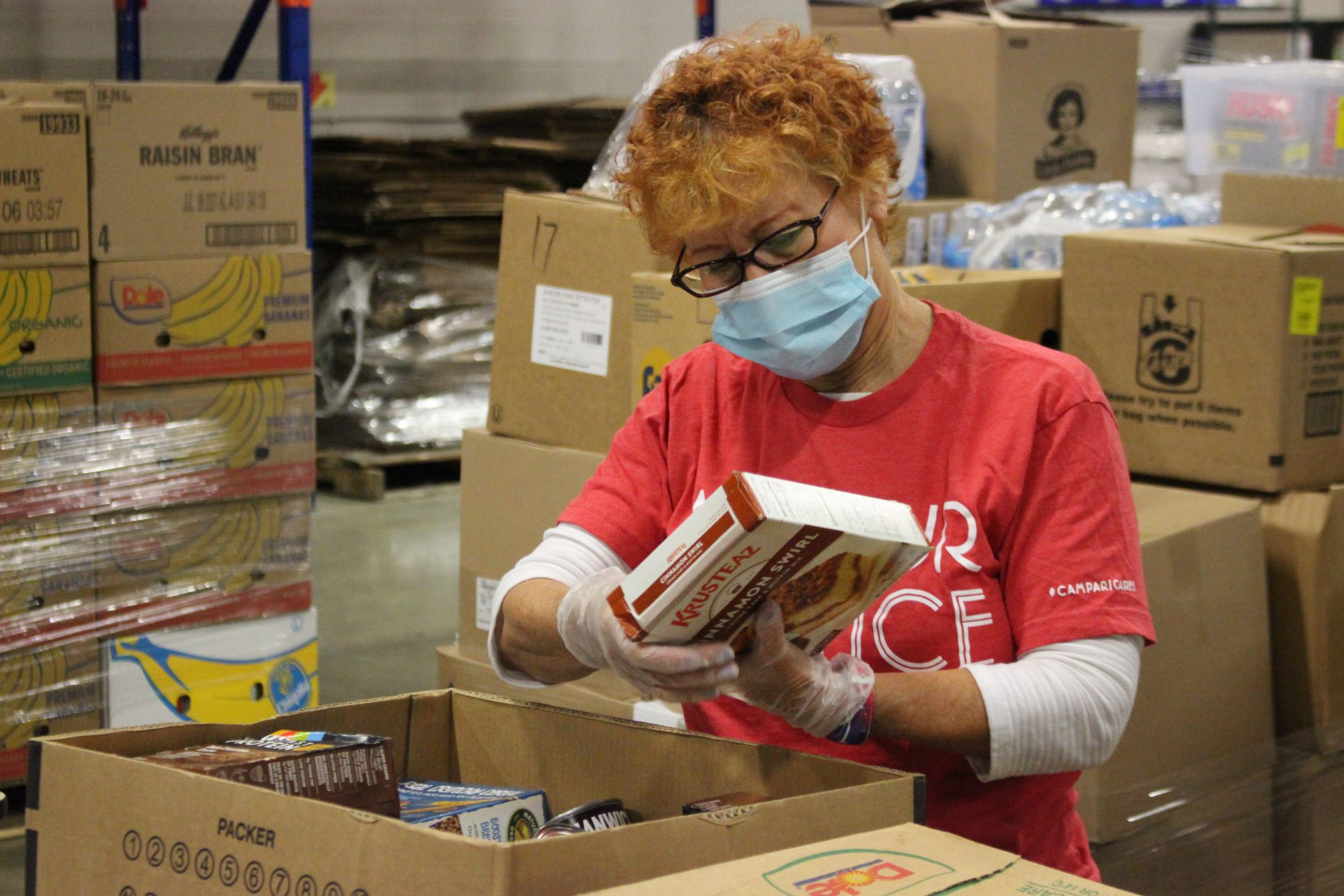 woman inspecting box greater cleveland food bank