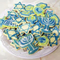 a plate of cookies decorated for Hanukkah: menorah, dreidel, and Star of David shapes with blue and white icing