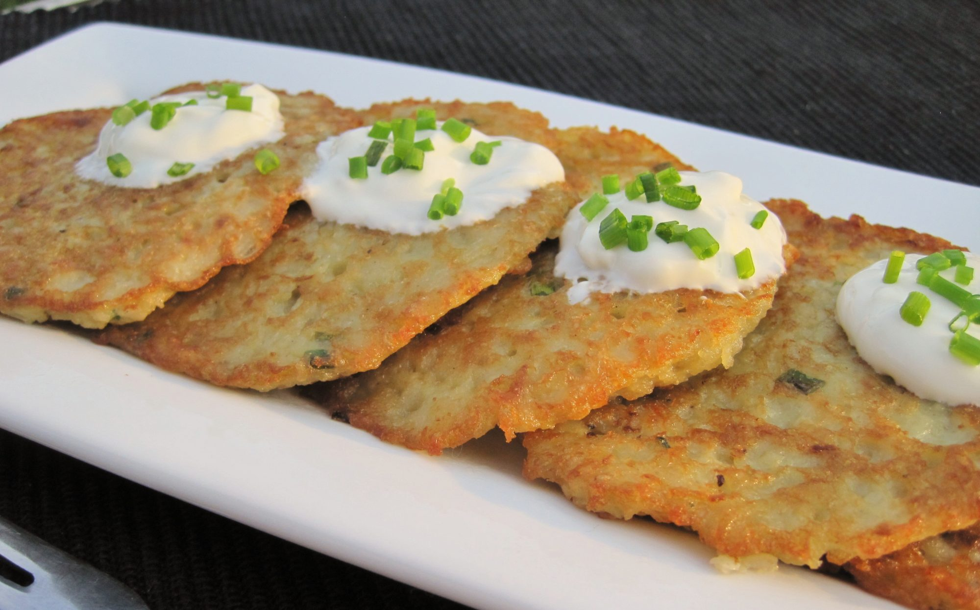 latkes topped with sour cream and chopped chives layered on a rectangular platter