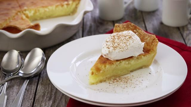 Slice of buttermilk pie with whipped cream on top.
