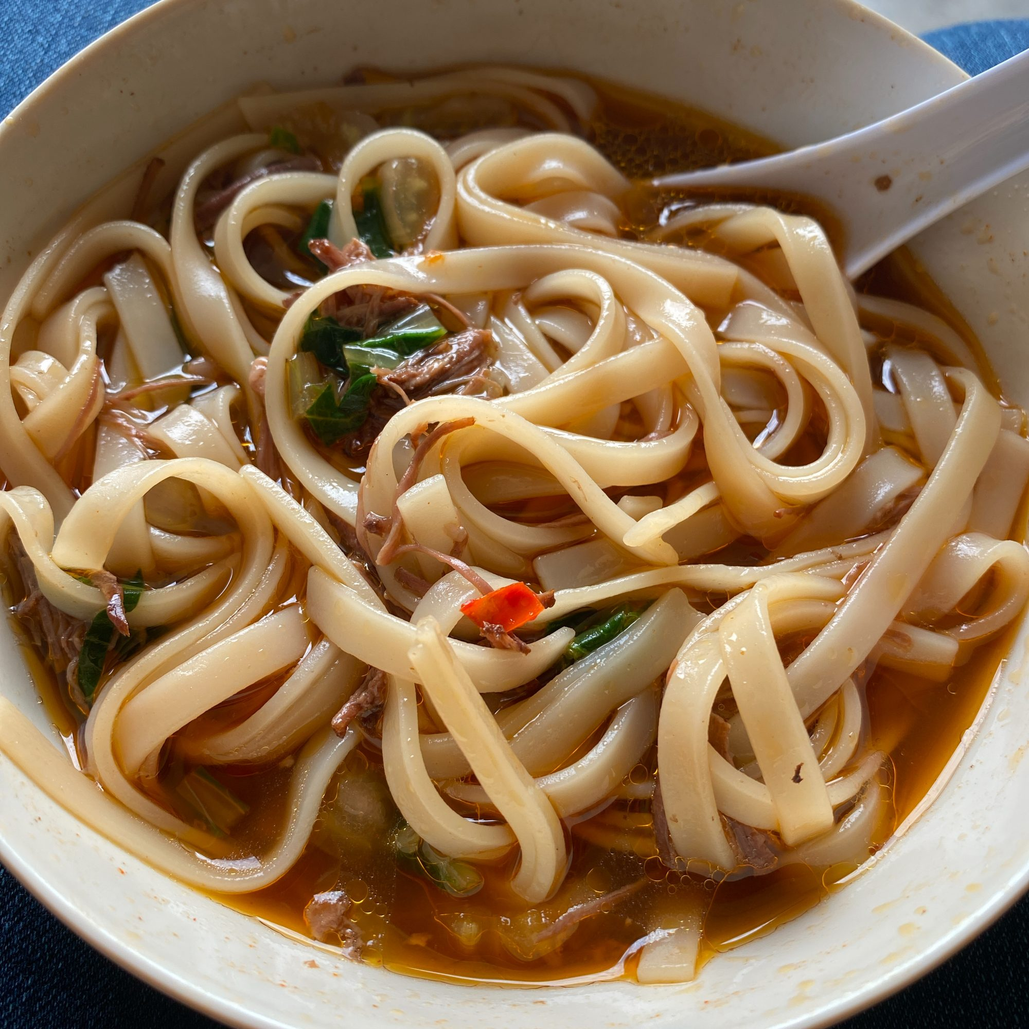 Taiwanese Spicy Beef Noodle Soup in a white bowl