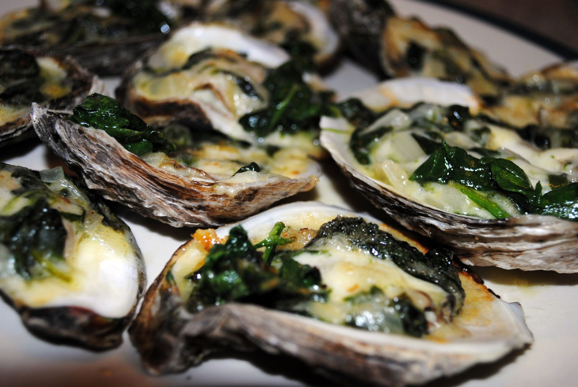 closeup of oysters on the half shell baked with spinach and cheese