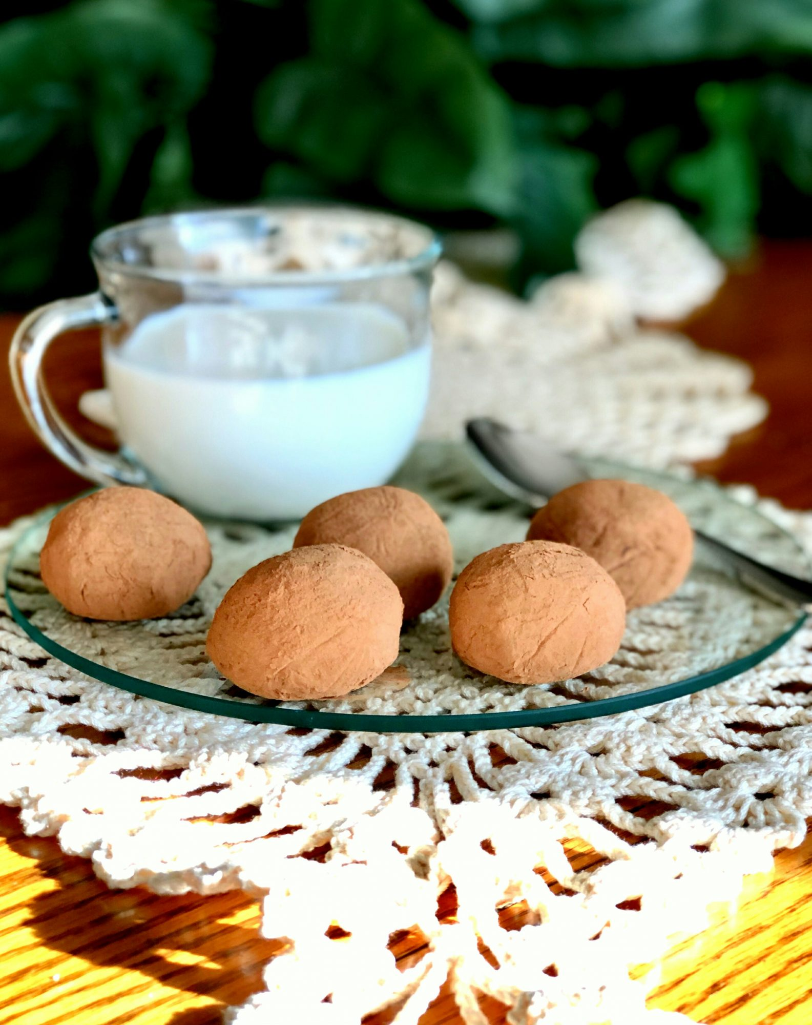 chocolate truffles on crystal glass plate with cup of milk