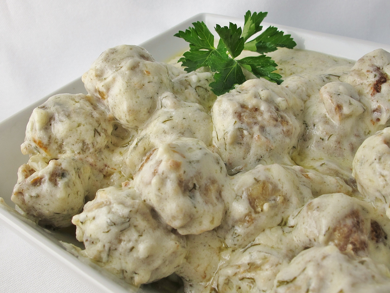 meatballs in a sour cream sauce garnished with a parsley sprig