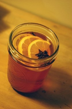 a mason jar of mulled alcohol fruit punch garnished with orange slices and star anise